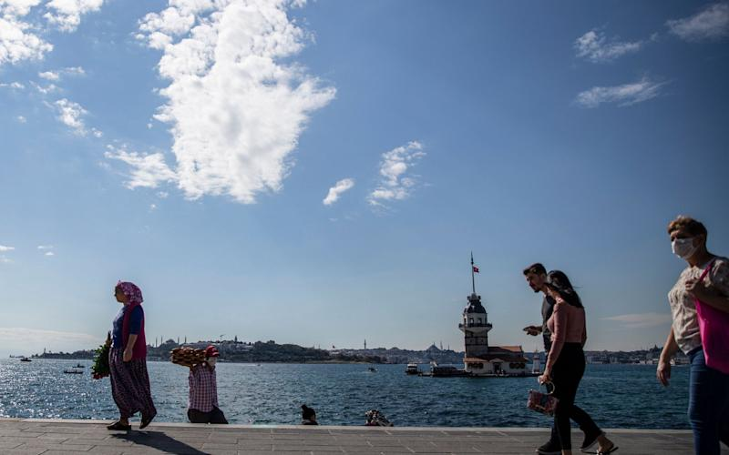 People spend time near the Bosphorus by the Maiden's tower and the Hagia Sophia Grand Mosque in Istanbul, Turkey - Shutterstock