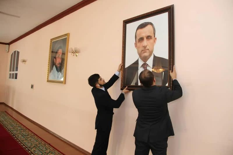 Afghan embassy staff hang a portrait of Afghan First Vice President Amrullah Saleh on the wall at the embassy in Dushanbe