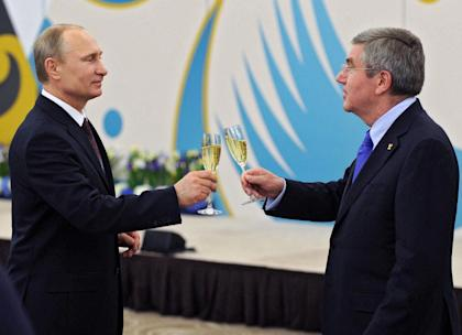Vladimir Putin, left, toasts a glass of champagne with IOC president Thomas Bach. (AP)