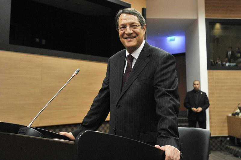 Cypriot President Nicos Anastasiades smiles before testifying to a judicial panel in Nicosia