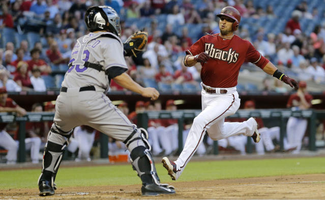 Arizona Diamondbacks' Martin Prado, right, tries to score on a base hit by teammate Paul Goldschmidt as Colorado Rockies catcher Jordan Pacheco waits for the throw during the first inning of a baseball game on Wednesday, April 30, 2014, in Phoenix. Prado was out on the play. (AP Photo/Matt York)