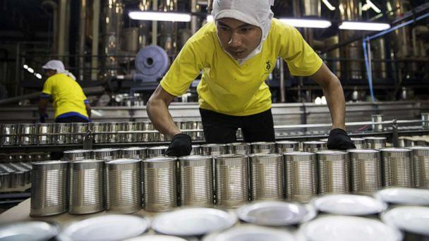 PHOTO: Workers move cans of pineapple at the Samroiyod Corp. fruit processing facility in Thailand, Dec. 1, 2017. (Bloomberg via Getty Images)