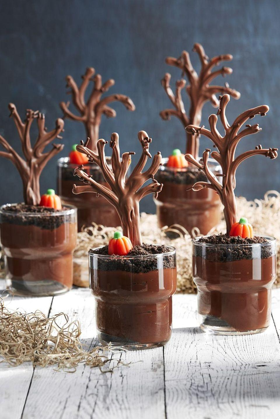 """<p>Bet your guests won't be able to get enough of these sweet treats! """"Spooky"""" chocolate trees meet crushed sandwich cookies and candy pumpkins in this fun Halloween dessert. </p><p><strong><a href=""""https://www.countryliving.com/food-drinks/a28943384/spooky-forest-pudding-cups/"""" rel=""""nofollow noopener"""" target=""""_blank"""" data-ylk=""""slk:Get the recipe"""" class=""""link rapid-noclick-resp"""">Get the recipe</a>.</strong> </p>"""