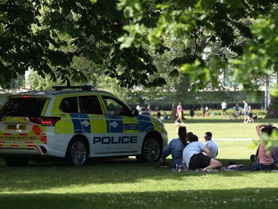 Police officers in a patrol car move sunbathers on in Greenwich Park (PA)