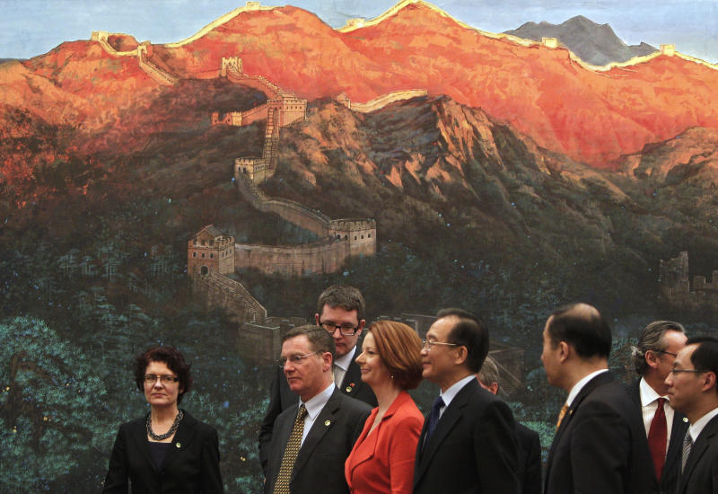 Australian Prime Minister Julia Gillard, in red, accompanied by Chinese Premier Wen Jiabao, walks past a painting of the Great Wall of China after a signing ceremony at the Great Hall of the People in Beijing Tuesday, April 26, 2011. (AP Photo/Andy Wong)