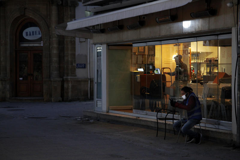 A man wearing a fask mask to protect againt coronavirus, handles his mobile telephone as he sits outside a shuttered cafe on the vacant Ledra Street in Nicosia, Cyprus, Sunday, April 26, 2020. Medical experts say the low number of new coronavirus infections is paving the way to start gradually lifting a strict day-at-home order that includes a night time curfew. (AP Photo/Petros Karadjias)