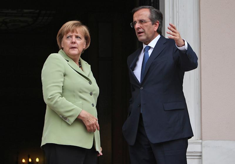 Greece's Prime Minister Antonis Samaras, right, and Germany's Chancellor Angela Merkel speak before their meeting at the Maximos mansion in Athens, Tuesday, Oct. 9, 2012. Amid draconian security measures and a mass protest, German Chancellor Angela Merkel arrived Tuesday for her first visit to Greece since the eurozone crisis began there three years ago. Her five-hour stop is seen by the Greek government as a historic boost for the country's future in Europe, but by protesters as a harbinger of more austerity and hardship. (AP Photo/Thanassis Stavrakis, Pool)