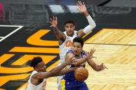 Indiana Pacers guard Malcolm Brogdon, center, passes the ball as gets caught between Orlando Magic center Wendell Carter Jr., let, and forward Chuma Okeke, back, during the second half of an NBA basketball game, Sunday, April 25, 2021, in Orlando, Fla. (AP Photo/John Raoux)