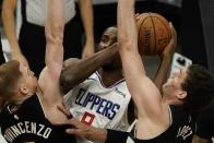 LA Clippers' Serge Ibaka tries to shoot between Milwaukee Bucks' Donte DiVincenzo and Brook Lopez during the first half of an NBA basketball game Sunday, Feb. 28, 2021, in Milwaukee. (AP Photo/Morry Gash)