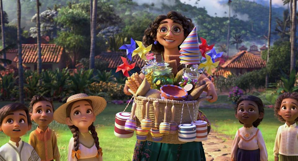 Mirabel holding a basket of knickknacks while surrounded by several children