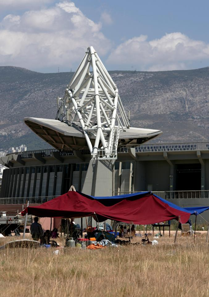 Makeshift tents are pitched in front of the Olympic beach volleyball stadium in Athens August 11, 2006. Barbed wire, padlocked doors and scattered garbage are what Athenians see these days at their multi-billion euro sports venues built two years ago for the 2004 Olympics. Picture taken Aug. 11, 2006. REUTERS/Yorgos Karahalis