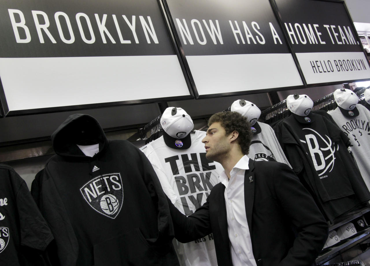 Brooklyn Nets basketball player Brook Lopez looks at team merchandise before a news conference to unveil the new team logos in the Brooklyn borough of New York, Monday, April 30, 2012. The Nets will be moving from New Jersey to the new Barclays Center in Brooklyn, New York for the 2012-2013 NBA basketball season. (AP Photo/Seth Wenig)