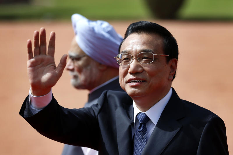 Chinese Premier Li Keqiang waves at the media in front of Indian Prime Minister Manmohan Singh during his ceremonial reception at the Indian President's palace in New Delhi, India, Monday, May 20, 2013. Li said Monday he chose India for his first foreign visit because cooperation between the world's two most populous nations is crucial to world stability and economic growth. He was visiting India just weeks after the two nations resolved a tense standoff between their troops over the disputed Himalayan border between their two countries. (AP Photo/Saurabh Das)