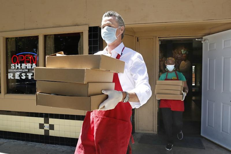 California Gov. Gavin Newsom, carries meals made at the Queen Sheba Ethiopian Cuisine restaurant, to a waiting delivery vehicle in Sacramento, Calif., Friday, June 19, 2020. Newsom, visited the restaurant, owned by Zion Taddese, right, that is participating in the Great Plates Delivered program that provides meals to older adults who are at-risk to COVID-19. (AP Photo/Rich Pedroncelli, Pool)
