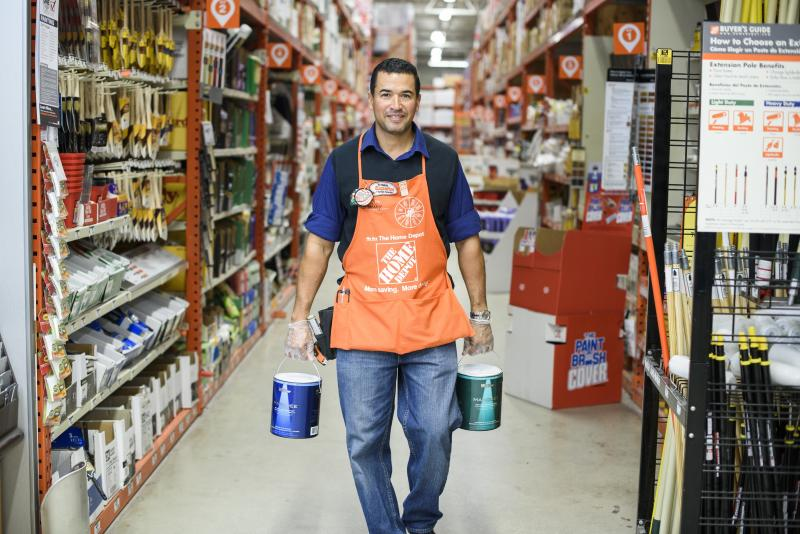 A Home Depot associate walks down a store aisle carrying two cans of paint.