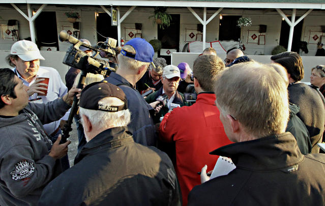 Trainer Art Sherman, center, speaks to the media about Kentucky Derby 140 winner California Chrome, outside Barn 20 at Churchill Downs in Louisville, Ky., Sunday, May 4, 2014. (AP Photo/Garry Jones)