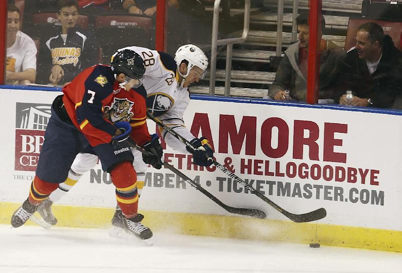 Florida Panthers' Dmitry Kulikov (7) and Buffalo Sabres Zemgus Girgensons battle for the puck during the first period of an NHL hockey game in Sunrise, Fla., Friday, Oct. 25, 2013. (AP Photo/J Pat Carter)
