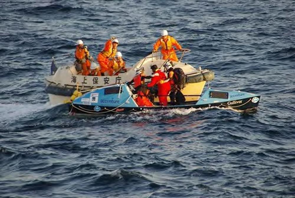 In this photo released by Japan Coast Guard, British adventurer Sarah Outen, center of foreground boat, is rescued by the Japan Coast Guard in the Pacific Ocean off northeastern coast of Japan, Friday, June 8, 2012. Outen's blog said she was hit by a storm during her attempted journey around the world, and that her boat rolled over and was damaged. Another Briton on a similar trek was still awaiting rescue. (AP Photo/Japan Coast Guard)