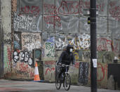 A cyclist wears a mask as he passes graffitti in London, Saturday, Jan. 23, 2021 during England's third national lockdown since the coronavirus outbreak began. The U.K. is under an indefinite national lockdown to curb the spread of the new variant, with nonessential shops, gyms and hairdressers closed, and people being told to stay at home. (AP Photo/Kirsty Wigglesworth)