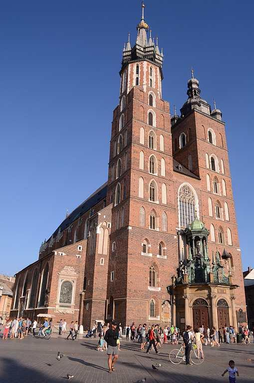 St Mary's Church, Krakow, Poland   Built in red brick with a wooden altar, the 14th century church rebuilt in Gothic style stands in the heart of Krakow and was built on the ruins of an earlier church, which was destroyed in a war. The church is characterised by two tall towers, a legend that refers to two brothers who built the church; one was murdered by the other due to jealousy. We wait near the Main Market Square to hear the trumpet played from atop the taller tower, a tradition that continues every day. The tradition, referred to as Hejnal Mariacki, is the playing of a Krakow anthem as a tribute to the 13th century bugler who was killed during a war when he tried to warn the people.
