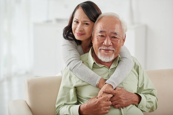 A married senior couple embracing one another.