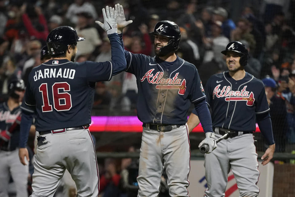 Atlanta Braves' Travis d'Arnaud, left, is congratulated by Dansby Swanson after hitting a three-run home run that scored Adam Duvall, right, and Austin Riley during the ninth inning of the team's baseball game against the San Francisco Giants in San Francisco, Friday, Sept. 17, 2021. (AP Photo/Jeff Chiu)