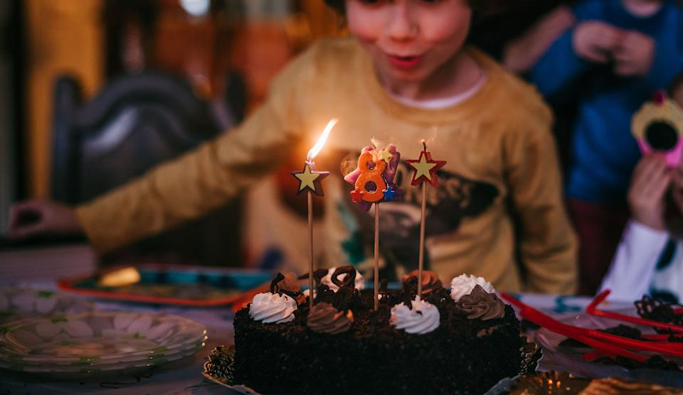 a boy blowing  out candles  in his birthday cake (Photo: Carol Yepes via Getty Images)