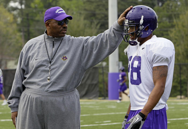 """In this  Friday, April 8, 2011 photo, East Carolina football coach Ruffin McNeill taps Emanuel Davis on the helmet during NCAA college football spring practice in Greenville, N.C.  The former Pirates' defensive back has lost 90 pounds since having weight-loss surgery in January. Next up is hip replacement surgery later this month, which will allow """"Coach Ruff"""" to walk easier and without pain. (AP Photo/Gerry Broome)"""