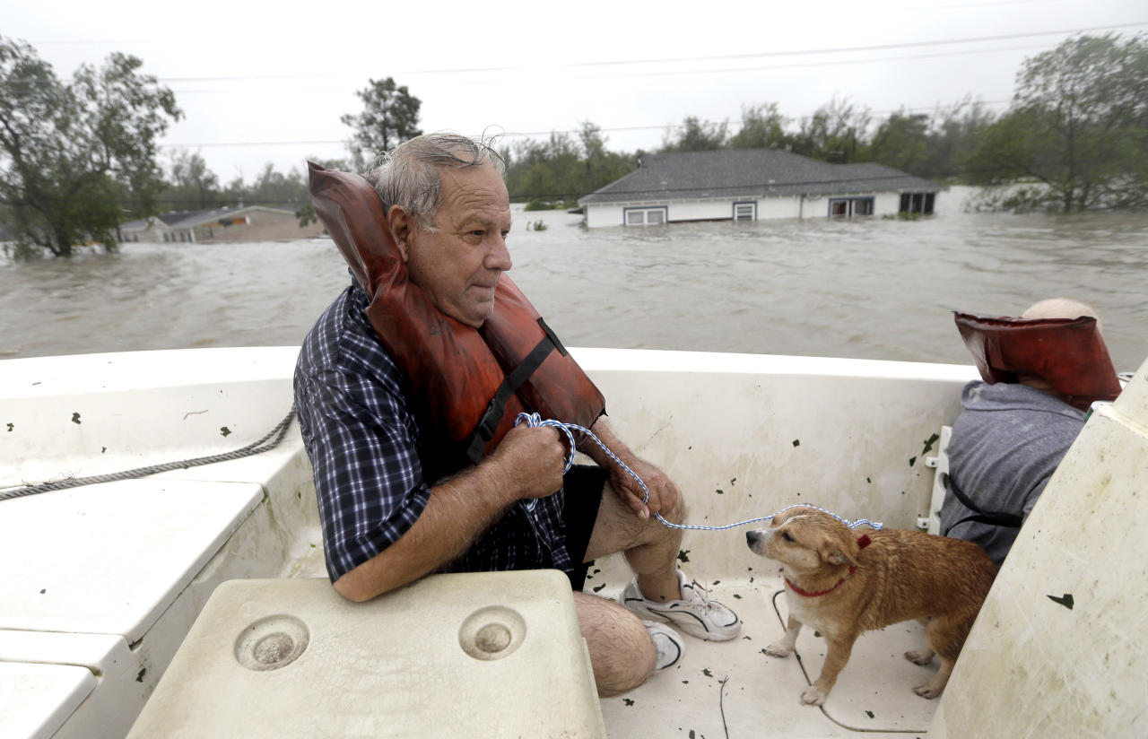 Carlo Maltese and his dog Pin ride in a boat after being rescued from his flooded home as Hurricane Isaac hits Wednesday, Aug. 29, 2012, in Braithwaite, La. (AP Photo/David J. Phillip)
