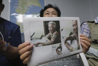 South Korean Shin Yun-sun shows photos of her 92-year-old mother, Baek Bong-rye, during an interview at her house in Seoul, South Korea Wednesday, July 29, 2020. Shin, 75, has spent decades pestering government officials, digging into records and searching burial grounds on Russia's desolate Sakhalin island, desperately searching for traces of a father she never met. Shin wants to bring back the remains of her presumably dead father for her ailing mother. Japan's colonial government conscripted Shin's father for forced labor from their farming village in September 1943, when Baek was pregnant with Shin.(AP Photo/Ahn Young-joon)