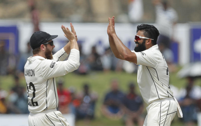 New Zealand's Ajaz Patel, right, is congratulated by Kane Williamson for the dismissal of Sri Lankan's Kusal Mendisduring the day five of the first test cricket match between Sri Lanka and New Zealand in Galle, Sri Lanka, Sunday, Aug. 18, 2019. (AP Photo/Eranga Jayawardena)