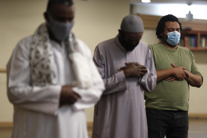 "Muslims pray as they practice social distancing during an evening prayer called ""tarawih"" marking the first eve of the holy fasting month of Ramadan at Chicago's Muslim Community Center on Monday, April 12, 2021. (AP Photo/Shafkat Anowar)"