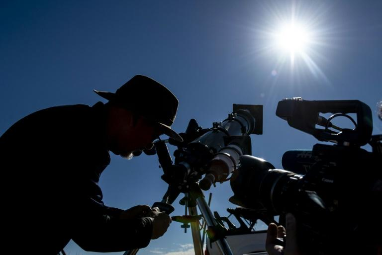 An astronomer looks at the sun through a telescope on the eve of a solar eclipse at La Higuera in Chile's Coquimbo Region on July 1, 2019 (AFP Photo/Martin BERNETTI)