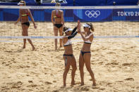 April Ross, left, of the United States, celebrate with teammate Alix Klineman a winning point during a women's beach volleyball match against Germany at the 2020 Summer Olympics, Tuesday, Aug. 3, 2021, in Tokyo, Japan. (AP Photo/Petros Giannakouris)