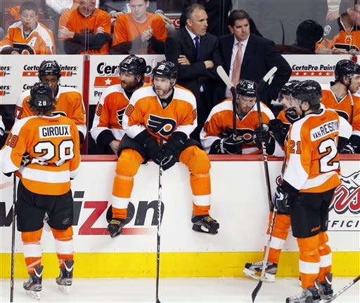 Down 3-1 the Philadelphia Flyers including Claude Giroux, left, Jaromir Jagr, sitting on the boards and James van Riemsdyk, right, wait during a timeout called by the New Jersey Devils during the third period in Game 2 of an NHL hockey Stanley Cup second-round playoff series, Tuesday, May 1, 2012, in Philadelphia. The Devils won 4-1 evening the best of seven series at 1-1.(AP Photo/Tom Mihalek)