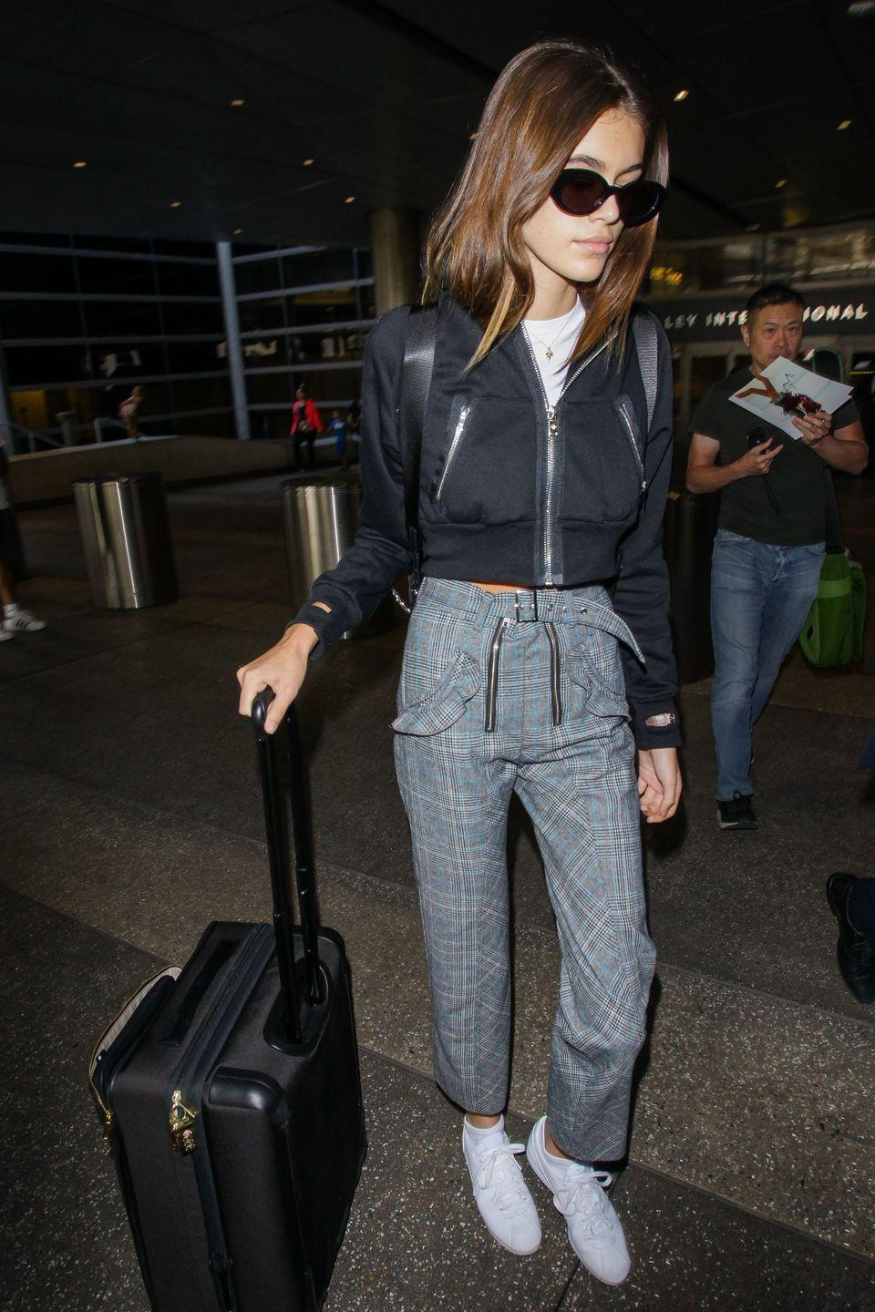 <p>The model was spotted wearing high-waisted checkered trousers and a black bomber jacket in LAX.</p>