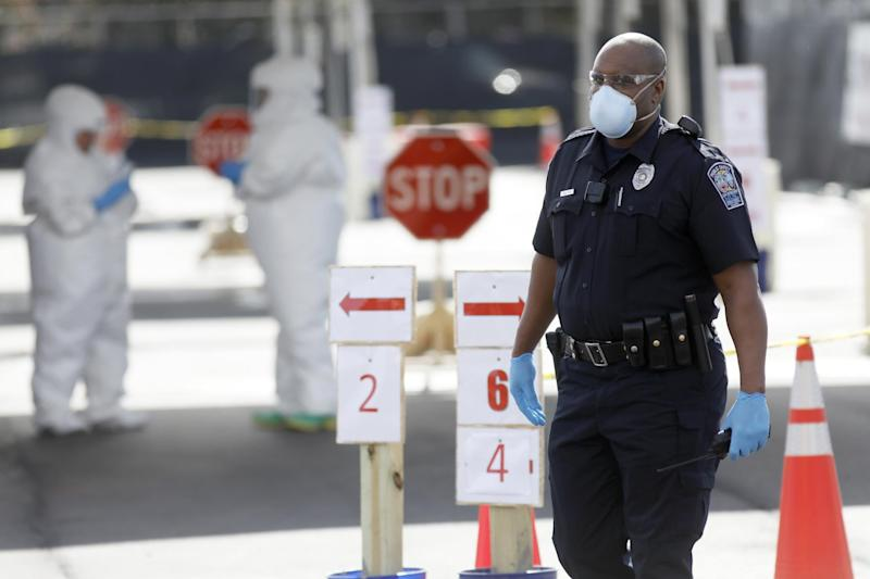 A Medical University of South Carolina public safety officer walks by the hospital's drive-through tent for patients who are being tested for coronavirus at the Citadel Mall parking lot in Charleston, South Carolina: AP Photo/Mic Smith