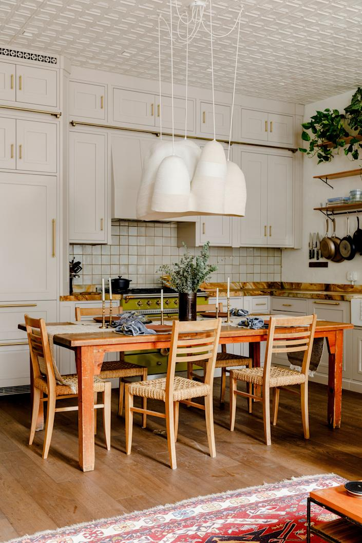 """The kitchen originally featured an island, but Harbour opted to swap it out for a farm table. Harbour admits he put a few change orders in as the renovation got under way, but the kitchen swap """"was one of the examples of a good change order, where it saved money!"""" he says. The unique pendant lamp above the table is from Doug Johnston."""