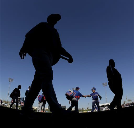 In this photo made with a fisheye lens, Chicago Cubs players walk off the field after an exhibition spring training baseball game against the Texas Rangers Wednesday, March 6, 2013, in Surprise, Ariz. (AP Photo/Charlie Riedel)