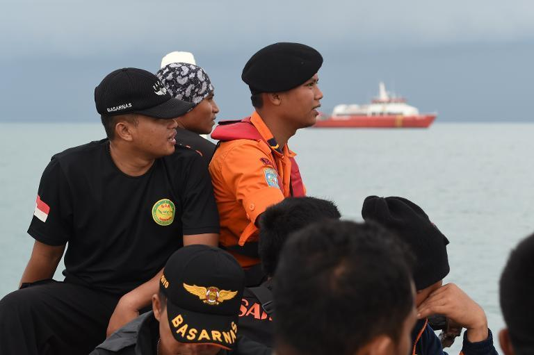 Members of an Indonesian search and rescue team are ferried out to a ship to conduct search operations at sea for missing AirAsia flight QZ8501 from Manggar in East Belitung