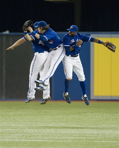 Toronto Blue Jays' Rajai Davis, right, Colby Rasmus, center, and Travis Snider celebrate their 10-4 win over the Oakland Athletics during a baseball game in Toronto, Thursday, July 26, 2012. (AP Photo/The Canadian Press, Aaron Vincent Elkaim)