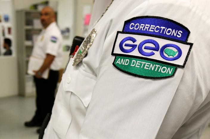 In 2017, an employee of the GEO Group wears a company patch on his uniform as he works at the Northwest Detention Center in Tacoma, Wash., during a media tour. (Photo: Ted S. Warren/AP)