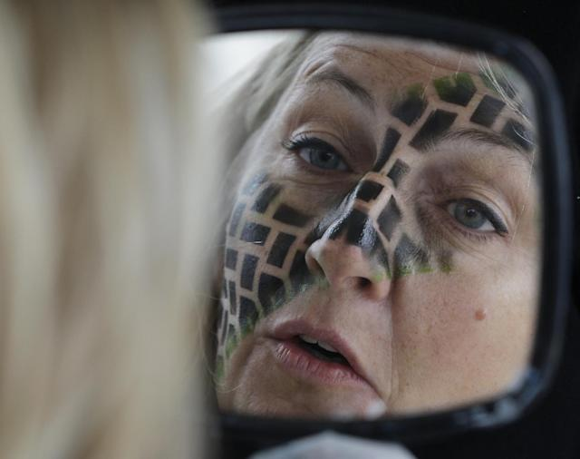 Veronika Smetazek checks her face, painted by Susan LeMaster, before the NASCAR Sprint Cup series auto race at Chicagoland Speedway in Joliet, Ill., Sunday, Sept. 15, 2013. (AP Photo/Nam Y. Huh)