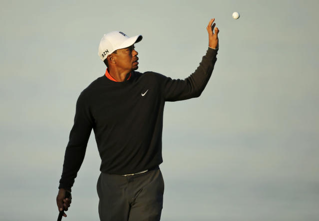 Tiger Woods reaches for his golf ball on the fourth hole during the pro-am at the Farmers Insurance Open golf tournament at Torrey Pines Golf Course on Wednesday, Jan. 22, 2014, in San Diego. (AP Photo/Chris Carlson)