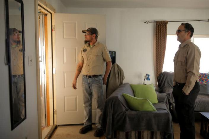 Kacey Dawson and Drew Miller stand inside the living room of a survival camp