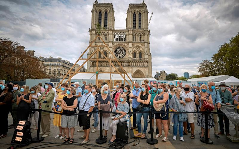 Parisians and tourists watch members watch the ongoing reconstruction of the Notre Dame Cathedral yesterday - Getty