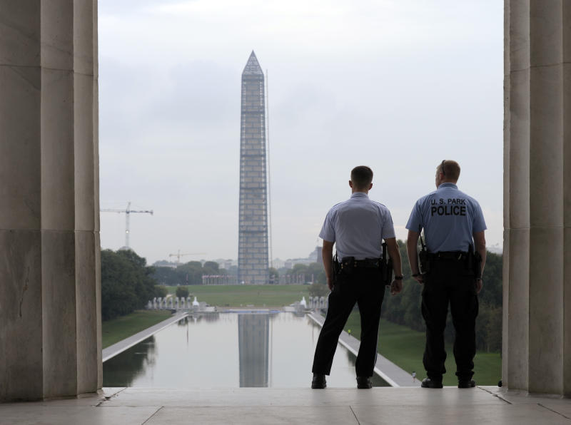 With the Washington Monument in the distance, Park Service police officers stand on duty at the Lincoln Memorial in Washington, Thursday, Oct. 17, 2013. Barriers went down at National Park Service sites and thousands of furloughed federal workers began returning to work throughout the country Thursday after 16 days off the job because of the partial government shutdown.(AP Photo/Susan Walsh)