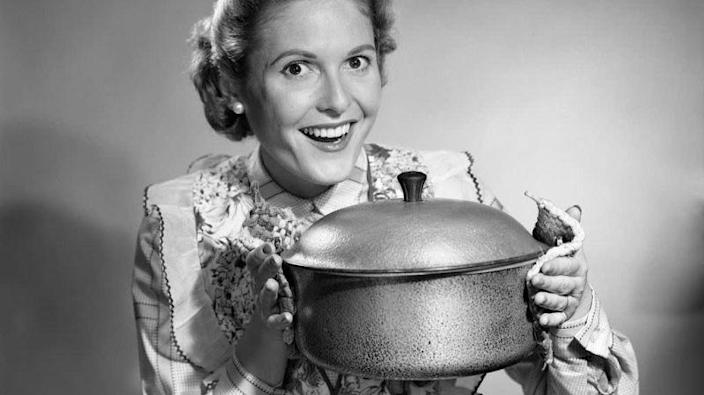 1950s housewife gleefully holds up Dutch oven