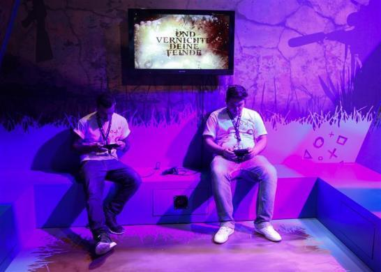 Visitors play Playstations at an exhibition stand during the Gamescom 2012 fair in Cologne August 15, 2012. The Gamescom convention, Europe's largest video games trade fair, runs from August 16 to August 19.
