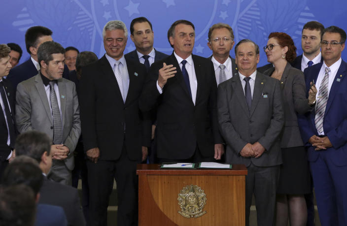 Brazil's President Jair Bolsonaro speaks during a signing ceremony where he signed a second decree that eases gun restrictions, at Planalto presidential palace in Brasilia, Brazil, Tuesday, May 7, 2019. The decree opens Brazil's market to guns and ammunition made outside of Brazil according to a summary of the decree. Gun owners can now buy between 1,000 -5,000 rounds of ammunition per year depending on their license, up from 50 rounds. Lower-ranking military members can now carry guns after 10 years of service. (AP Photo/Eraldo Peres)